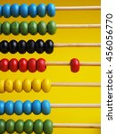 Small photo of Close up colorful abacus, traditional abacus in front of yellow background concept, selective focus.