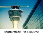 Flights management air control tower and passenger terminal in Munich international airport with flying plane in clear sky. Stock photo with split toning effect.