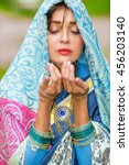 Small photo of Middle age woman in blue sari and Indian adornment poses in garden
