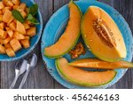 Cantaloupe melon slices sitting on blue rustic plate on wooden tabletop with two spoons and bowl filled with melon pieces - stock photo