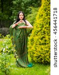 Small photo of Brunette young woman in sari and Indian adornment poses near to green bush in park