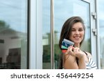 Small photo of Girl got a good deal. She smiles holding discount card in her hand against the glass storefront
