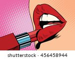 girl paints her lips with red... | Shutterstock .eps vector #456458944