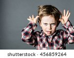 Small photo of angry little brat enjoying making a grimace, sticking out his tongue, playing with his hands for misbehavior, contrast effects, grey background