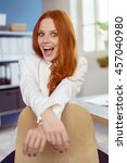 Small photo of Vivacious attractive young redhead woman leaning on the back of her chair at the office looking at the camera in amazement with her mouth agape