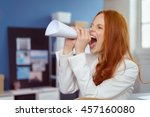 Small photo of Young businesswoman using a paper megaphone in the office made from a rolled up page of paper to get the attention of a colleague