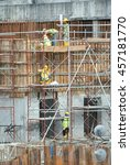 Small photo of MELAKA, MALAYSIA -JULY 05, 2016: Construction workers wearing safety harness and adequate safety gear while working at high level at the construction site in Melaka, Malaysia.