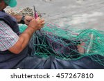 Fishing Nets Being Mended By...