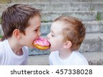 two kids bite off a donut and... | Shutterstock . vector #457338028