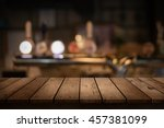 Stock photo wooden table with a view of blurred beverages bar backdrop 457381099