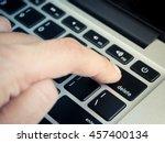 finger pushing delete key on...