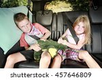 Stock photo brother and sister fighting in the back of a car 457646809