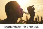 young man drinking water from a ...   Shutterstock . vector #457785256