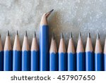 Small photo of Standing out of the crowd. Being different concept. A row of perfect pencils with one broken. A symbol of disfigurement.