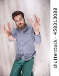 Small photo of crazy gay men make faces. Man have grown whiskers.VERY funny guy hipster bewhiskered. Gay men on the floor BEAUTIFUL freak. heavy beard.Funny emotions on the man's face