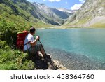 hiker relaxing by ossoue lake ... | Shutterstock . vector #458364760