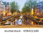 Stock photo bicycle parked on a bridge in amsterdam at night netherlands 458422180