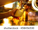male hand poured beer indoors | Shutterstock . vector #458456530