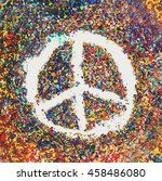 Small photo of Peace symbol on scraps of colorful pastel oil colors