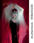 Small photo of female zombie in a misty mystical garb on red background