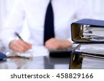Small photo of Binders with papers are waiting to be processed with business woman back in blur. Accounting planning budget, audit and insurance concept