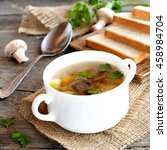 Small photo of Diet mushroom soup with vegetables, sliced white bread on a kitchen cutting board, spoon, parsley, fresh agaricus on a wooden table. Lenten mushroom soup in a bowl and on a burlap. Closeup