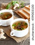 Small photo of Home mushroom soup in a bowl, wheat bread slices on a cutting board, fresh raw agaricus and green parsley on a wooden table. Vegetable soup with champignons recipe. Closeup