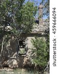 Small photo of Entranceway to a falling vintage adobe house with a still-intact brick chimney on the southern plains of New Mexico, surrounded by trees - vertical orientation