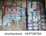 Small photo of Baan Song, Suratthani / Thailand - July 23, 2016 : Old and color waned commercial posters on Asian style wooden doors of a dilapidated house.