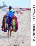 Small photo of pedlar of cloth and towels on the beach