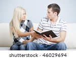 Attractive couple tussling over a book. Horizontal shot. - stock photo