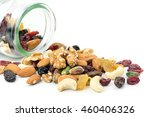 Small photo of Mixed nuts and dried fruits spilt from bottle isolated on white background