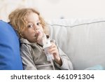 Small photo of Close-up of a little boy with sad expression on his face, using an inhalator