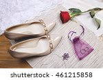 Small photo of Beige high heels lackered shoes with golden buckle, white gold amethyst necklace, wedding rings and red rose flower on the table. Bride accessories