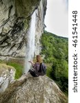 Small photo of Hiker young woman with backpack sitting on a rock while admiring the spectacular waterfall