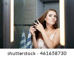 Young Woman Brushing Hair In...