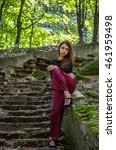 Small photo of Young charming teenager girl with long dark hair is a graceful gait destroyed by an ancient staircase the steps in Striysky Park in Lviv