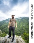 Small photo of Hiker standing on top of a mountain admiring the view