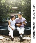 Small photo of Senior Couple Ukulele Romantic Fountain Concept