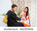 Small photo of Indian good looking young brother and sister celebrating Raksha Bandhan / Rakhi festival or on Bhai dooj/Bhau-Beej with Poja Thali, sweets, gifts or taking selfie pictures - Season's Greeting Card