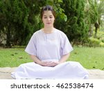 Small photo of meditation woman nature,Buddhist thai woman happy with white clothing sitting for concentration on green grass background.