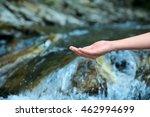 Female hand in water stream - stock photo