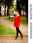Small photo of Elegant beautiful brunette with thoughtful look intriguing walks in the park in a red sweater with a nice warm autumn weather on a background vase with red flowers. Selective Focus. steps easy gait