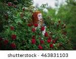 Stock photo gothic girl with red hair near the bushes of purple and red roses in the summer garden fashion 463831103