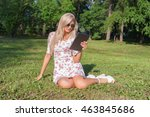 Girl sitting on the grass in the park among the trees and use the Internet on your tablet. Wireless internet connection. wifi and 3g connection. Social networking and chat for mobile communication.