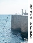 Small photo of ACRE, ISRAEL - AUGUST 03, 2016: Young man jumps to the sea from the top of the ancient walls of Acre, Israel. A combination of multiple exposure of the same jump