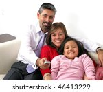 Beautiful happy family with TV remote control - stock photo
