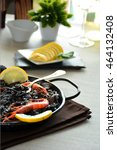 Small photo of paella of rice black with Squid, accompanied of wine white