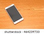 white mobile on wooden desk | Shutterstock . vector #464239733