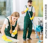 Small photo of Young professional cleaners cleaning accurate spacious apartment. Man mopping the floor and girl polishing the table